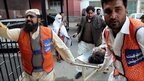 A man injured in the attack is taken to a hospital in Peshawar by medics