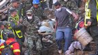 Colombian soldiers and a local resident carry a victim's body in Bello, near Medellin