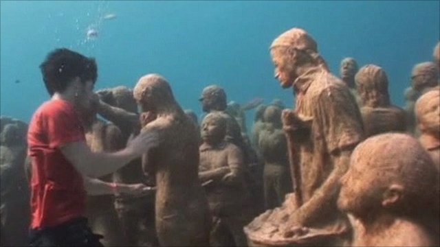 Greenpeace activist underwater with human sculptures