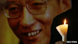 A protester holds a candle near a portrait of Liu Xiaobo at a vigil in Hong Kong