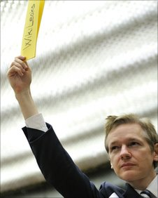 Julian Assange holds a piece of paper, saying Wikileaks