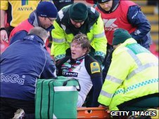 Ollie Smith is helped onto the stretcher in Sunday's defeat at Vicarage Road