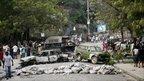 Haitians make their way between barricades in Port-au-Prince, 8 December 2010