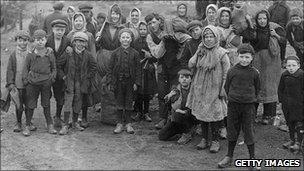 Children, wearing clogs, gather coal in 1921