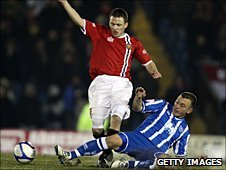 FC United's Matthew Wolfenden is challenged by Gary Hart of Brighton