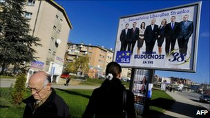 Kosovo Albanians walk past an election advertisement in Pristina (8 Dec 2010)