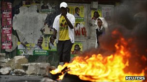 Haitians walk past a burning barricade in Port-au-Prince during protests against the election result