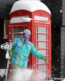 Skier outside phone box in Britain