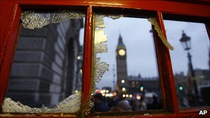 Houses of Parliament seen through broken window of phone box