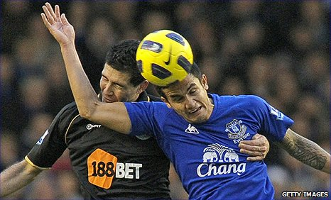 Everton midfielder Tim Cahill (right) beats Wigan defender Antolin Alcaraz to a header