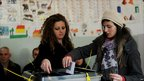 A young Kosovo Albanian woman (r) casts her ballot at a polling station in Pristina