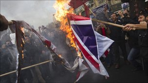 Iranian university students burn a British flag during a protest outside the British embassy in central Tehran December 12, 2010.