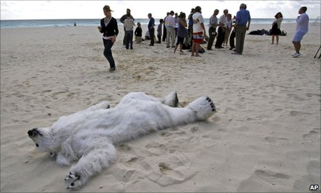 Man dressed in polar bear suit playing dead on Cancun beach (AP)