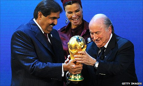 Fifa president Sepp Blatter presents the World Cup trophy to Qatar's Emir Sheikh Hamad bin Khalifa Al-Thani