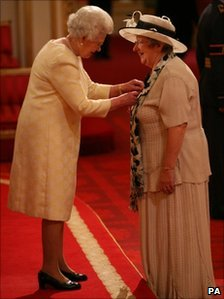 The Queen presents an MBE medal to Susan Morgan in November 2010