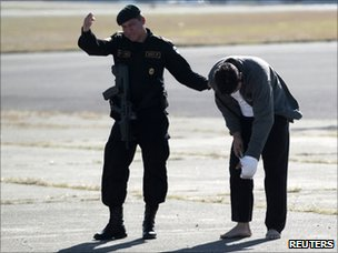 Guatemalan police officer escorts a suspected member of the Zetas at Guatemala City airport on 9 December 2010