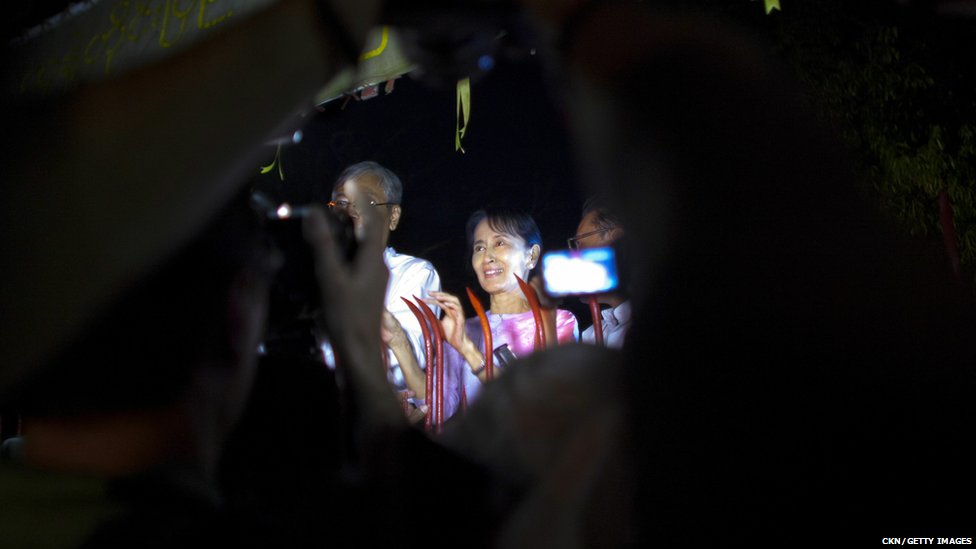 Opposition leader Aung San Suu Kyi (C) greets crowds of well-wishers at the gate of her house following her release from house arrest, on November 13, 2010 in Yangon, Burma