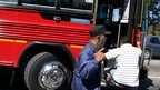 A private security guard oversees a passenger getting on a bus. Photo Taken March 2009.