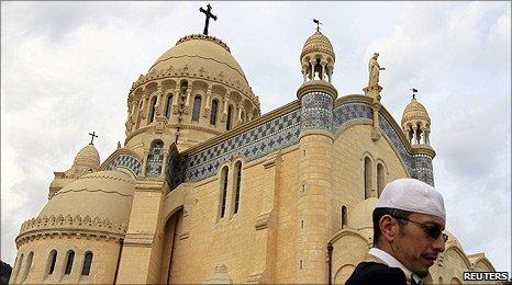 A man walks past Notre Dame d'Afrique