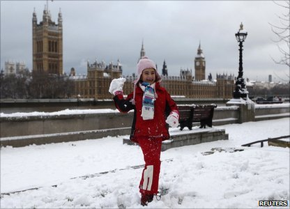 A young girl throws a snowball opposite the Houses of Parliament