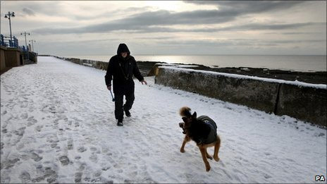 Man and dog take walk through snow on Porthcawl seafront