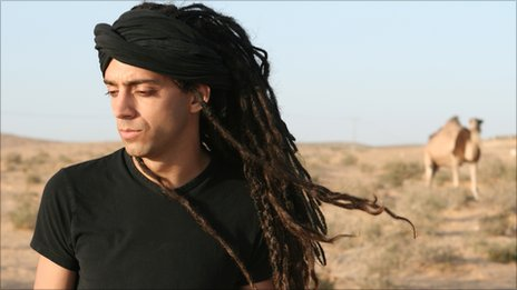 Idan Raichel in the desert in Israel with a camel behind. Photo by Bartzi Goldblat.