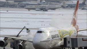 Workers defrost a plane at Heathrow Airport