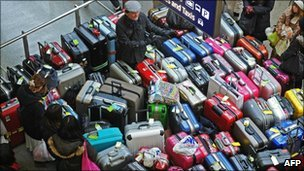 A passenger surrounded by luggage inside London's St Pancras International train station