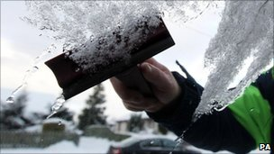 A motorists de-ices a car