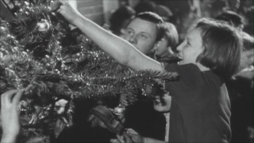 London children decorating a Christmas tree on a Tube station platform during the Blitz