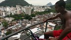 "A teenager looks out at downtown Rio from a ""pacified"" Santa Marta, one of Rio's oldest slums, or favelas, on 7 December 2009 in Rio de Janeiro, Brazil."