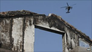 South Korean helicopter flies over house on Yeonpyeong island destroyed by North Korean shelling