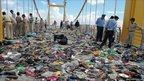 Cambodian police officials examine hundreds of shoes and other belongings on a bridge in Phnom Penh.