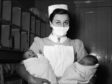 A 1950s midwife with two babies