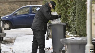 Police officer searching through bins