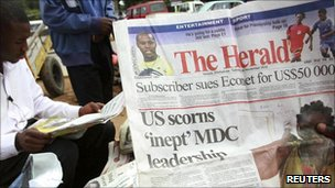 Zimbabweans read copies of the state owned Herald newspaper on the streets of Harare 3 December 2010