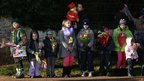 Children wait to present the UK's Queen Elizabeth II with flowers in Sandringham, England.