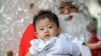 Toddler meets Father Christmas at the Jakarta Cathedral in Indonesia