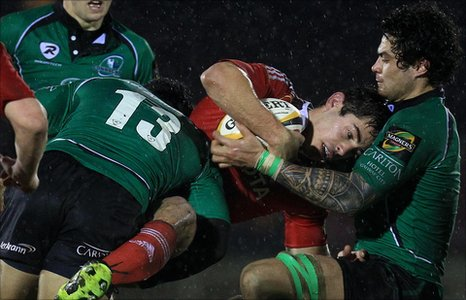 Munster's Tom Gleeson is tackled by Niva Ta'auso and Erza Taylor
