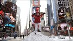 Child jumps off a snow pile in Times Square