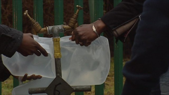 People collecting water in containers