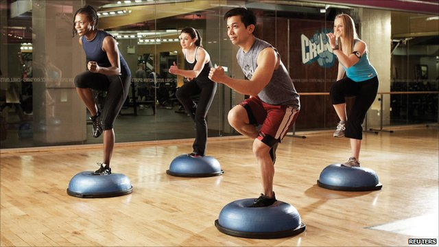 Four people exercising in a gym