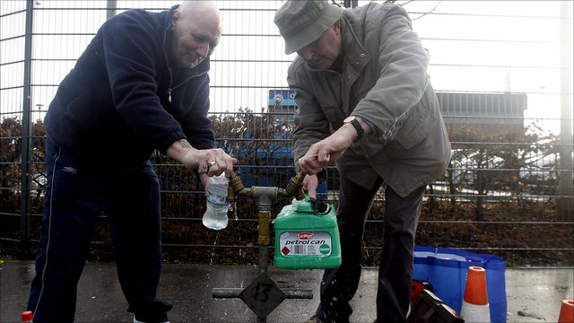 People fill containers with water from a pipe on the Boucher road in Belfast, Northern Ireland