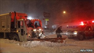 Snow plough digging out an ambulance