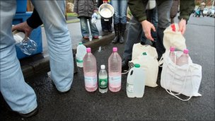 People filling up bottles and containers with water