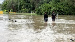 Two residents walk through floods in Emerald on 30 December 2010