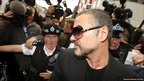 British singer George Michael is escorted out of Highbury Corner Magistrates Court in London