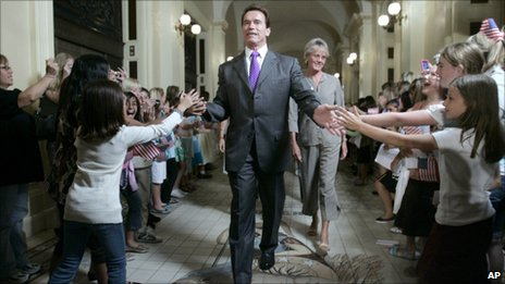 Arnold Schwarzenegger slapping the hands of school children