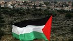 Palestinian flag being waved in front of a Jewish settlement.