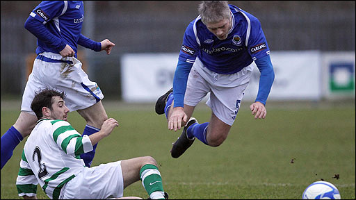 Ciaran Muir's challenge sends Linfield defender William Murphy flying at Suffolk Road
